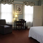 Hotel Coolidge room with king bed, desk, chair, and tv