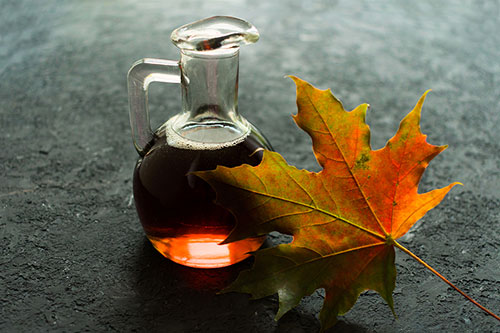Bottle with maple syrup and maple leaf on a black background